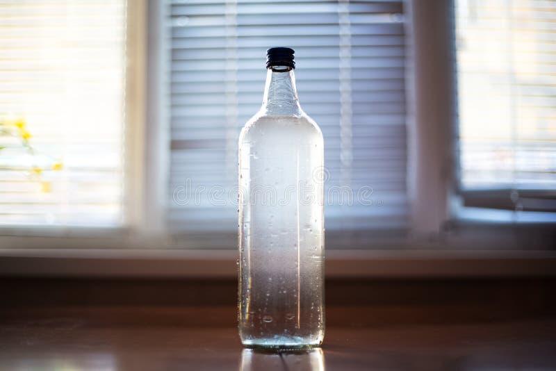 Glasflaska med vatten på tabellen arkivfoton