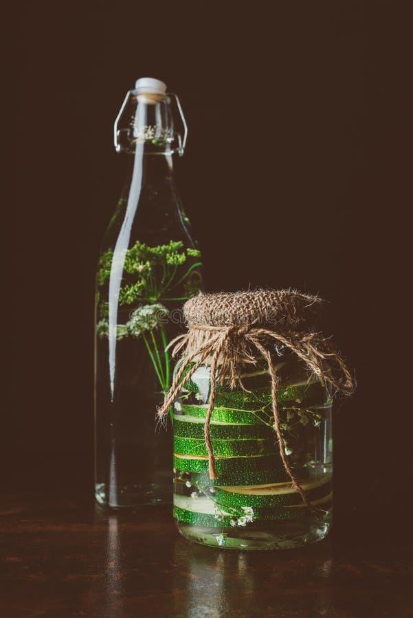 glasflaskan med vatten och dill och exponeringsglas skorrar med zucchinin på trätabellen royaltyfri bild