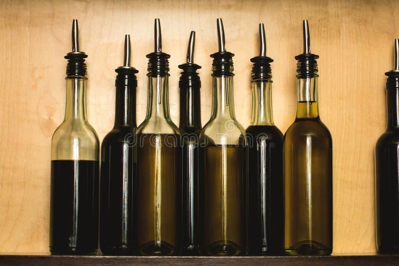 Glasflaskor av sunda olivoljor som arrangera i rak linje på ett hem- skåp Stillebendetaljsikt av en träkökhylla med genomskinligt royaltyfria foton