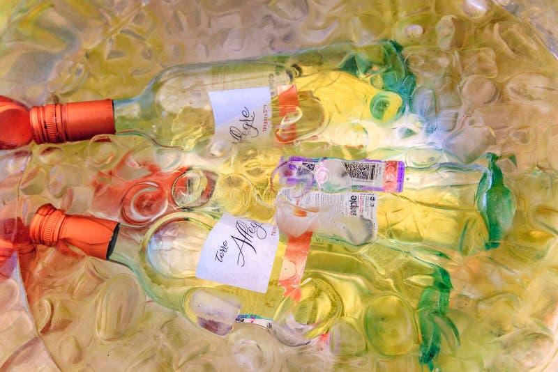 Glasflaskor av torrt vitt vin som ner kyler i kallt vatten bland istegelstenar arkivbild
