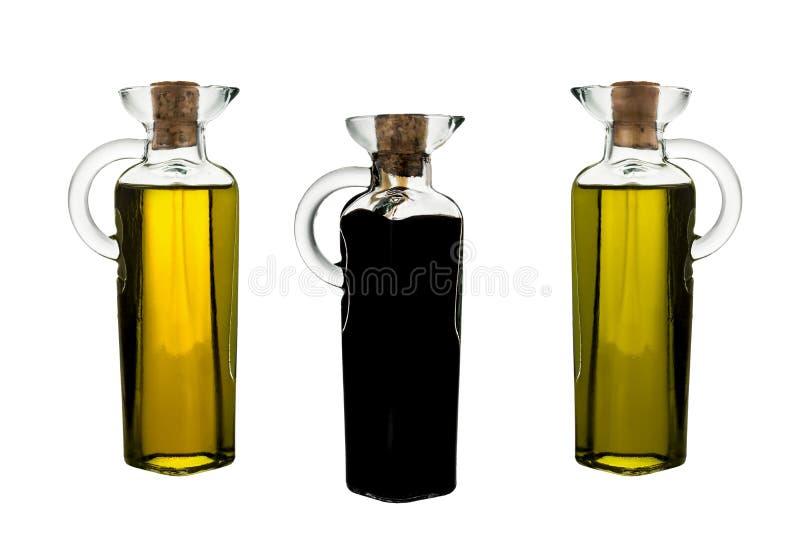 Glasflaskor för oskuldolivolja itu och isolerad modena balsamic vinäger arkivfoto