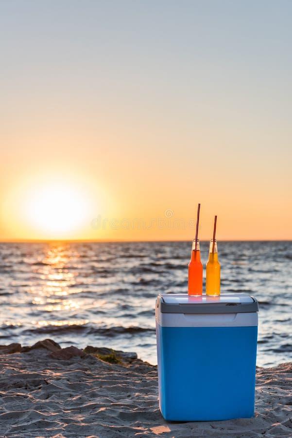 glasflaskor med sommardrycker och sugrör på kylare på den sandiga stranden royaltyfri foto