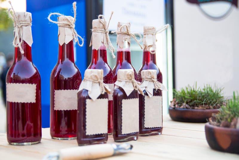 Glasflaskor med Tkemali sås arkivbilder