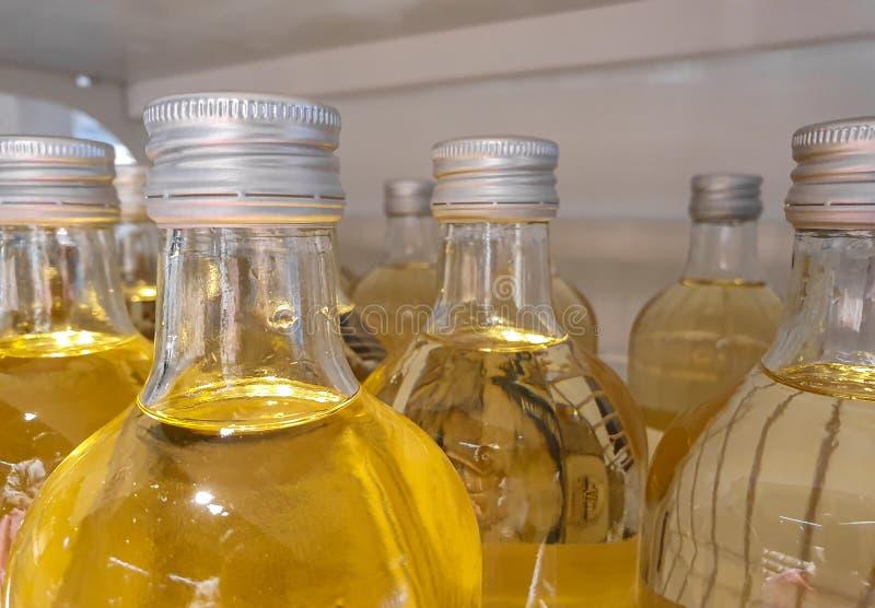 Glasflaskor som fylls med äppelmust arkivfoton