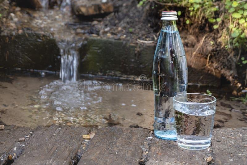 Glasfles en glas met water op de achtergrond van aard Bronwater stock afbeeldingen