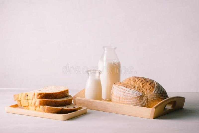 Glasfles melk met brood op houten die dienblad op witte achtergrond voor voedsel en gezond concept wordt geïsoleerd Met exemplaar stock afbeeldingen