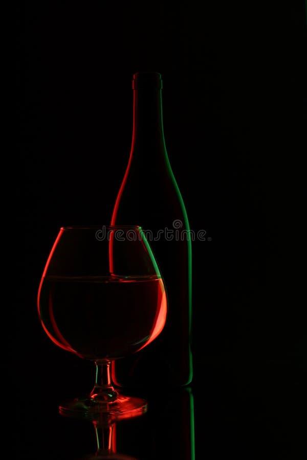 Glasfles van wijn en wijnglas stock afbeeldingen