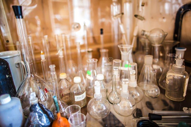 Glasflessen, reageerbuizen, flessen en koppen in een oud chemisch laboratorium stock foto