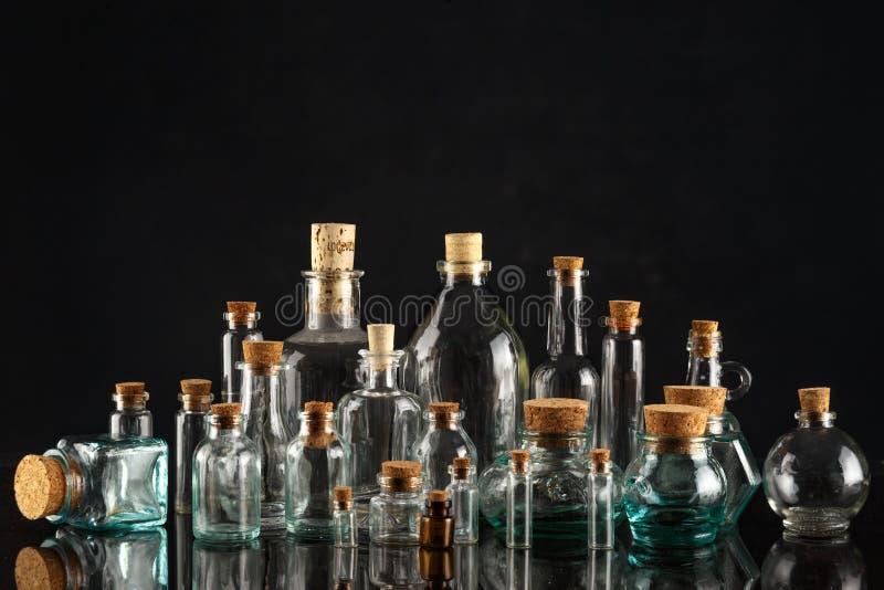 Glasflessen van verschillende vormen en grootte op een zwarte achtergrond stock fotografie