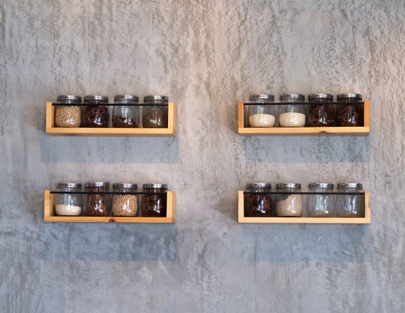 Glasgefäß auf hölzernen Regalen auf Holzbeton lizenzfreie stockbilder