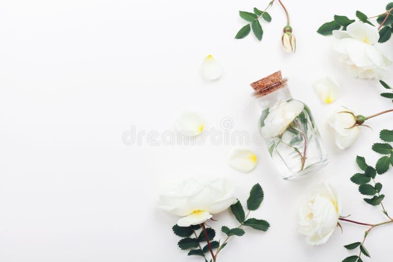 Glasgefäß mit Aromawasser und Weißrose blüht für Badekurort und Aromatherapie Draufsicht und flache Lageart lizenzfreie stockbilder