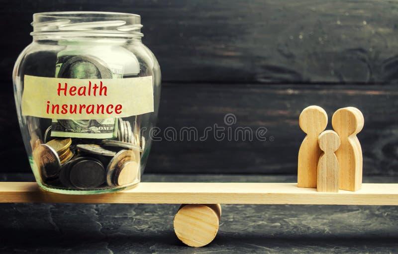 Glasgefäß mit Geld und die Wörter 'Krankenversicherung und die Familie auf den Skalen Das Konzept der Krankenversicherung des Leb lizenzfreies stockbild