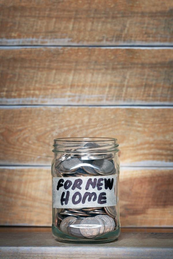 Glasgefäß mit Geldmünzen und eine Aufschrift auf dem Aufkleber ` für neues Haupt-` auf einem weißen Hintergrund stockfotos
