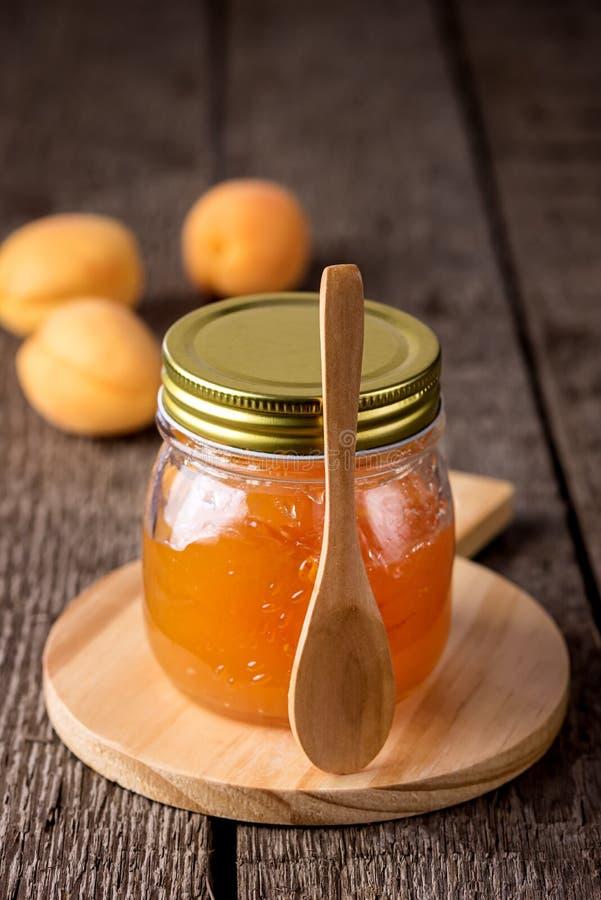 Glasgefäß selbst gemachte geschmackvolle Aprikosen-Marmelade und reife Aprikosen auf der hölzernen Hintergrund-Vertikale lizenzfreie stockbilder
