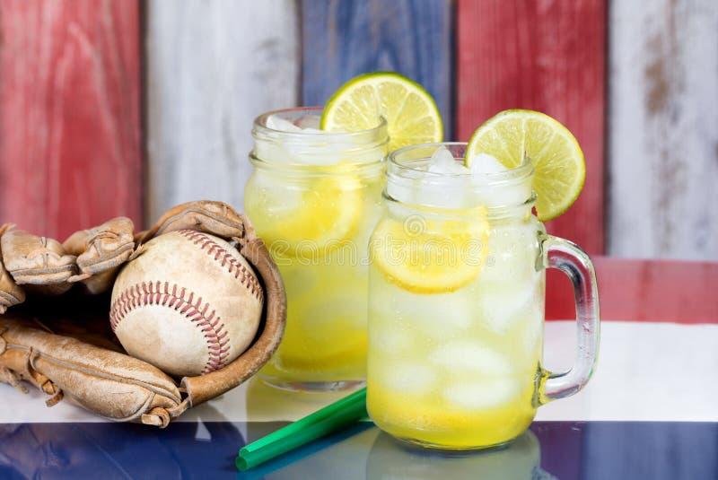 Glasgefäße füllten mit kalter Limonade und Baseballhandschuh mit Ball lizenzfreie stockbilder