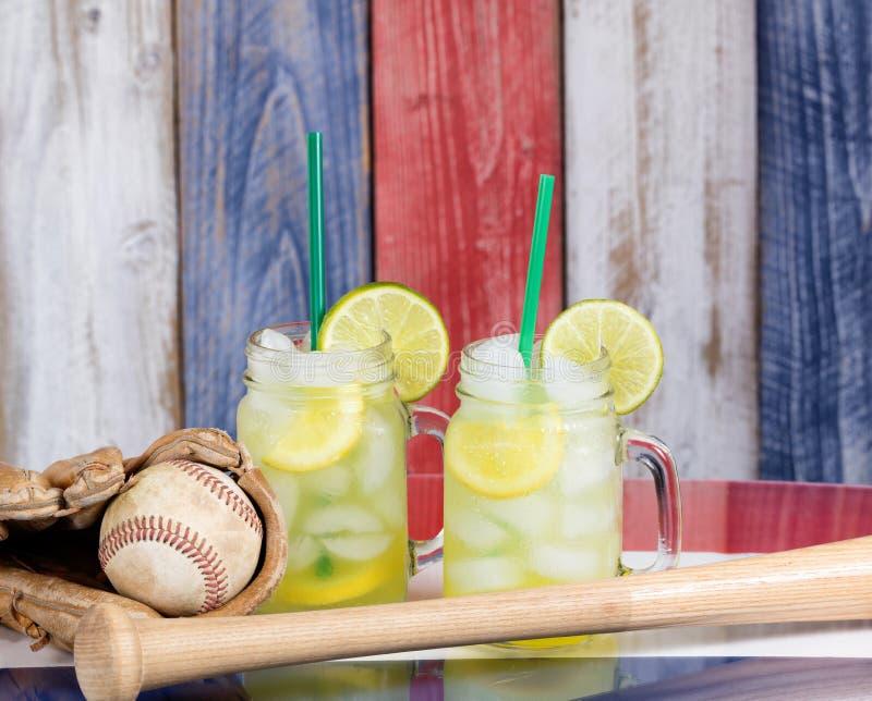 Glasgefäße füllten mit kalter Limonade zusammen mit Baseball sportin lizenzfreie stockfotos