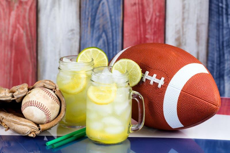 Glasgefäße füllten mit kalter Limonade zusammen mit Sport- Gegenständen lizenzfreie stockbilder