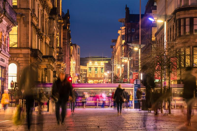 Pedestrians walking along the brightly lit Buchanan street in the city centre at night. Glasgow / Scotland - February 15, 2019: Pedestrians walking along the royalty free stock photos