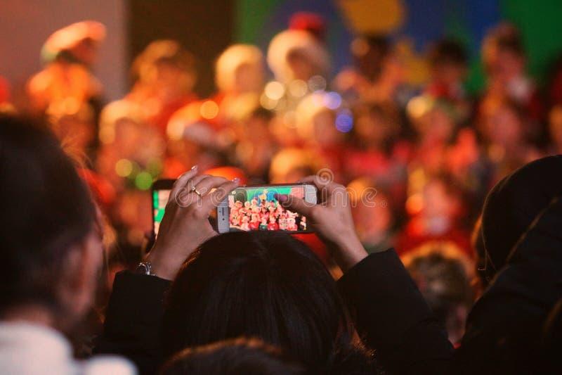 Glasgow UK: 14th December 2018 - förälder som antecknar deras barn under en Kristi födelselek på jultid i en av de primära royaltyfri foto