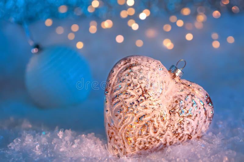 Glashart en bal op een sneeuw en een gestemde vage blauwe achtergrond van het schitteren bokeh met lichten De decoratie van Kerst royalty-vrije stock foto's