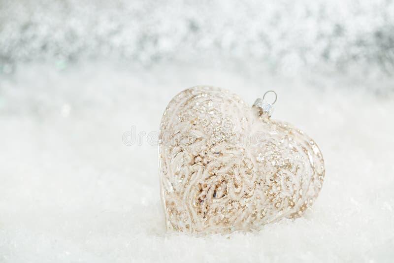 Glashart op een sneeuw Vage witte achtergrond van het schitteren bokeh met het gloeien lichten De decoratie van Kerstmis De ruimt stock afbeeldingen
