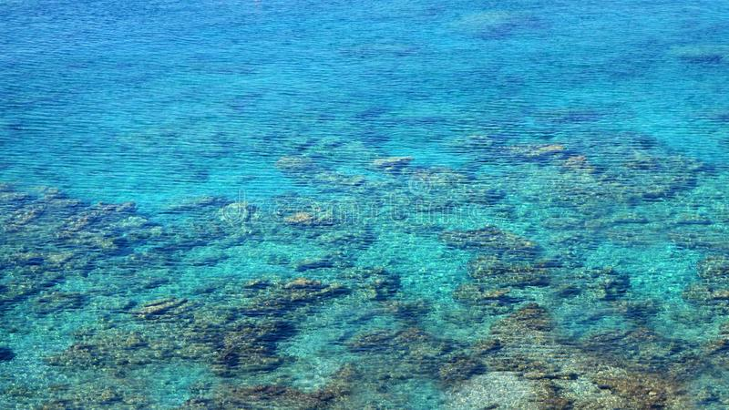 Glasheldere blauwe overzeese oppervlakte met steenbodem, overzeese achtergrond, watertextuur royalty-vrije stock afbeeldingen