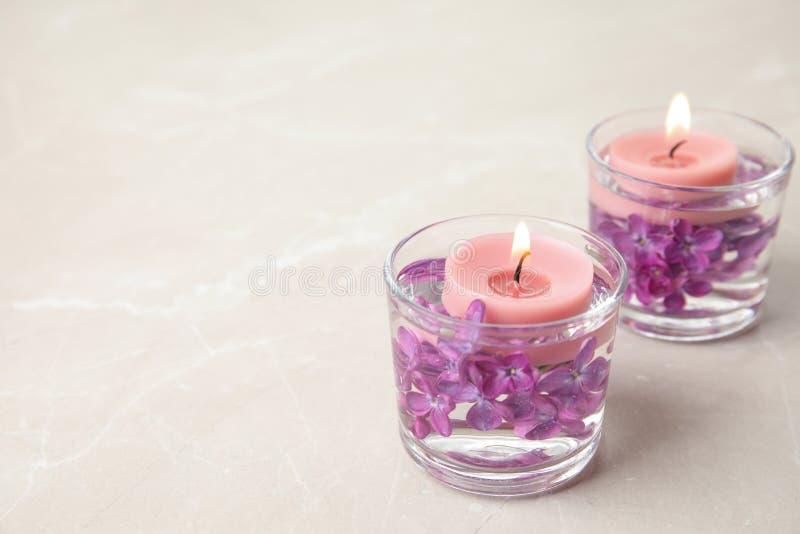 Glashouders met water, lilac bloemen en brandende kaarsen royalty-vrije stock foto