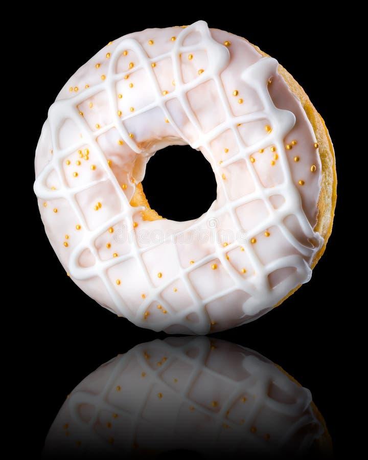 Glasierte Donut mit Sprinklen auf schwarzem Hintergrund, in drei Vierteln gedreht stockfotografie