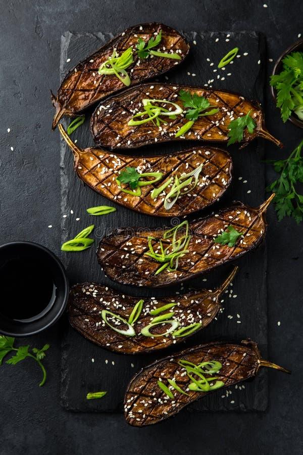 Glasig-glänzende gegrillte Auberginen dienten mit Samen des indischen Sesams und grünem onio lizenzfreies stockfoto