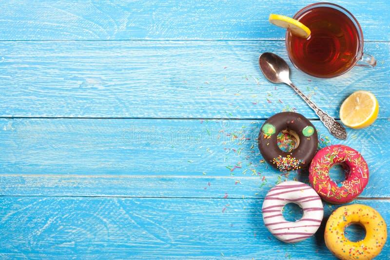 Glasig-glänzende Schaumgummiringe mit einer Tasse Tee auf einem blauen hölzernen Hintergrund mit Kopienraum für Ihren Text Beschn lizenzfreies stockfoto