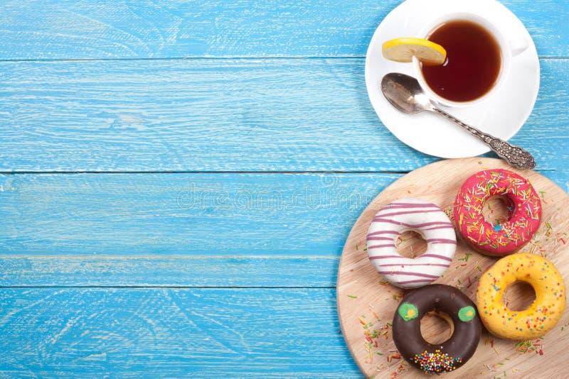 Glasig-glänzende Schaumgummiringe mit einer Tasse Tee auf einem blauen hölzernen Hintergrund mit Kopienraum für Ihren Text Beschn lizenzfreie stockbilder