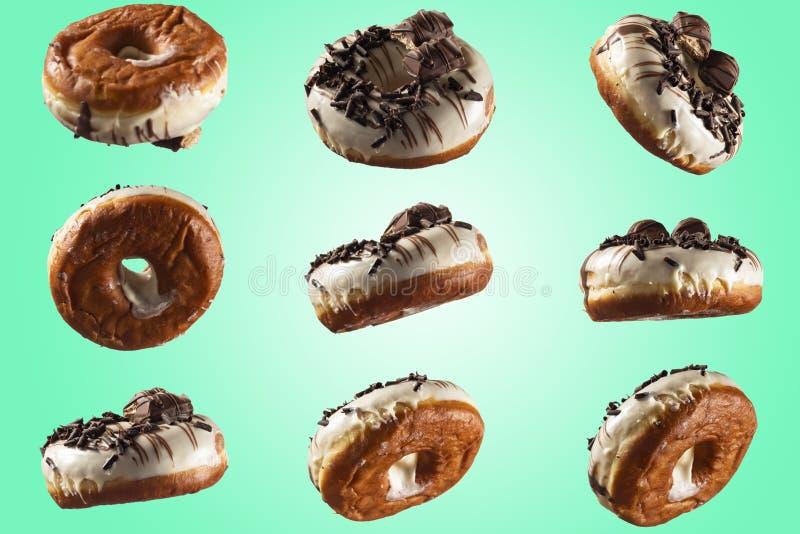 Glasig-glänzender Donut der weißen Schokolade und Schokolade, die auf blauem grünem Hintergrund übersteigt stockfotografie