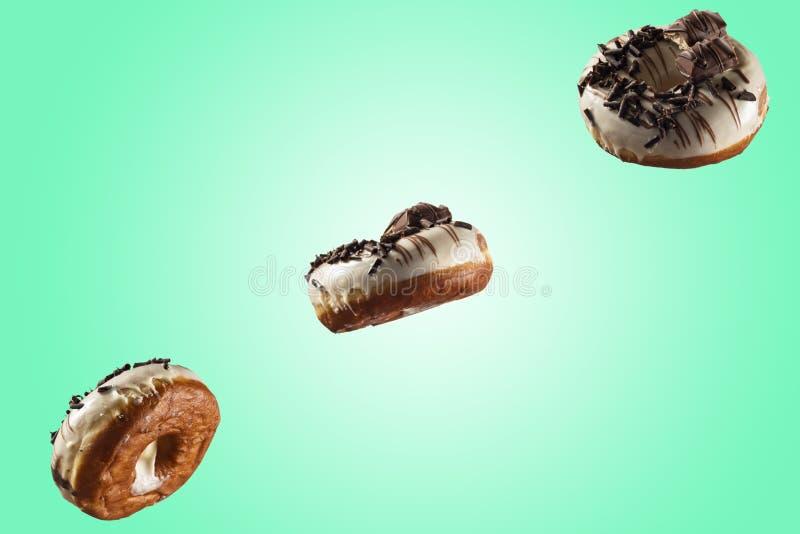 Glasig-glänzender Donut der weißen Schokolade und Schokolade, die auf blauem grünem Hintergrund übersteigt lizenzfreie stockbilder
