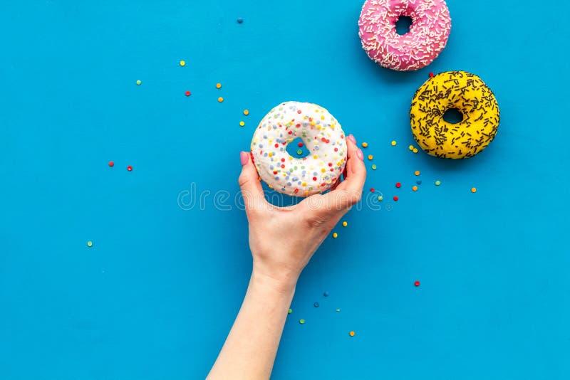 Glasig-gl?nzender verzierter Donut in der Hand f?r s??en Bruch auf flachem gelegtem Kopienraum des blauen Hintergrundes stockfotografie