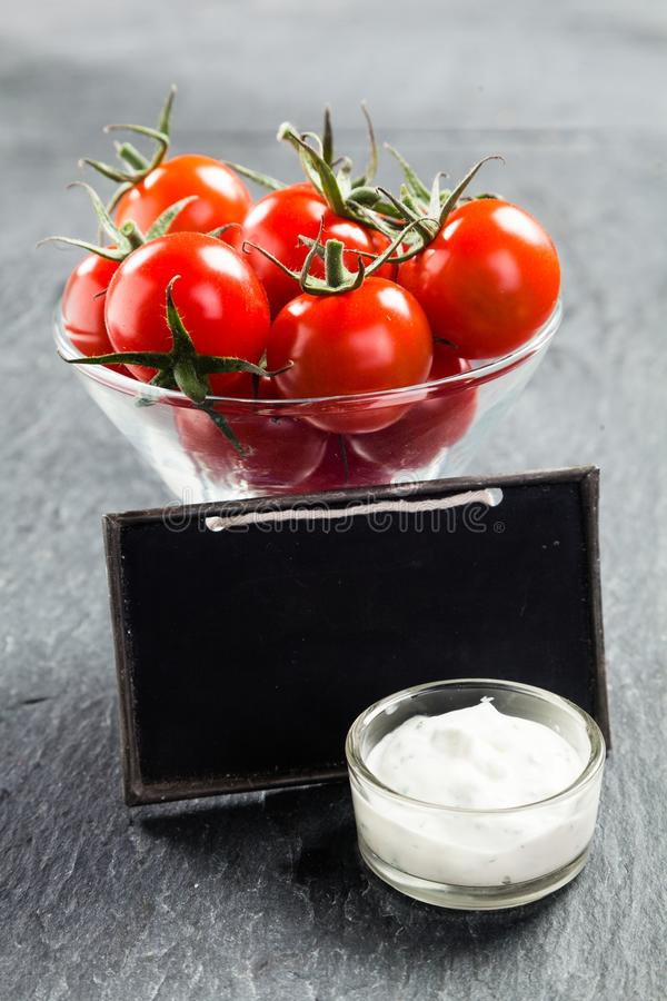 Glaskom kersentomaten en smakelijke saus stock foto