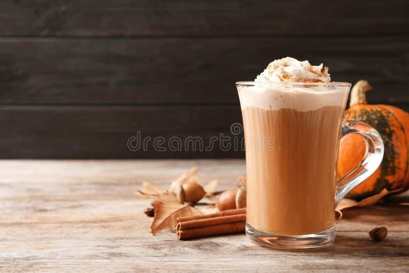 Glaskop met smakelijk pompoenkruid latte op houten lijst royalty-vrije stock afbeeldingen