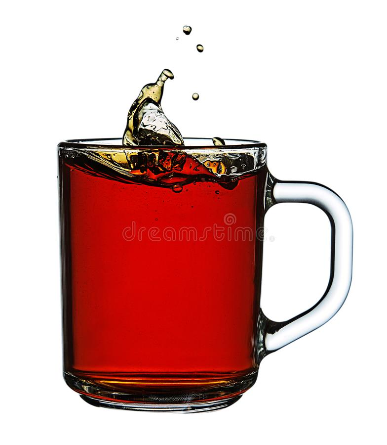 Glaskop thee op witte achtergrond met dalingswater en plons die wordt geïsoleerd stock afbeeldingen