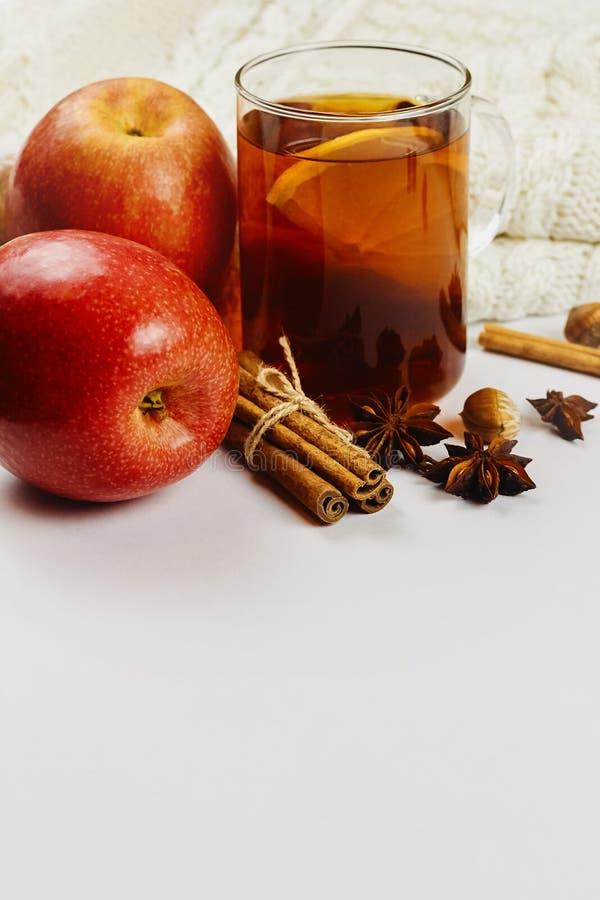 Glaskop van heet kruidig T-stuk met appelplakken, kaneel en anijsplant op witte gebreide achtergrond met exemplaarruimte royalty-vrije stock afbeelding