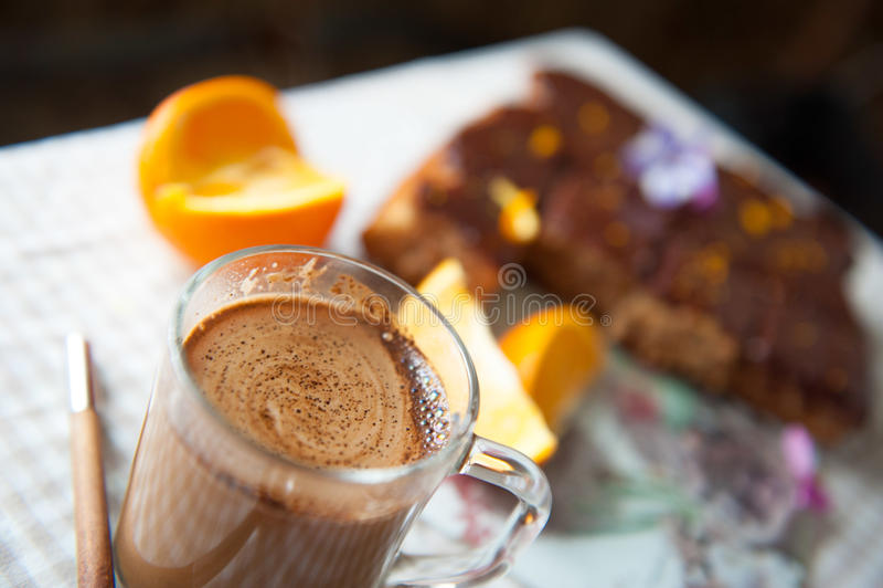 Glaskop van koffie met cake en een sinaasappel op de achtergrond stock foto