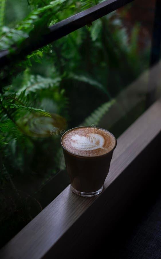 Glaskop van koffie met melk gevormd blad royalty-vrije stock afbeeldingen