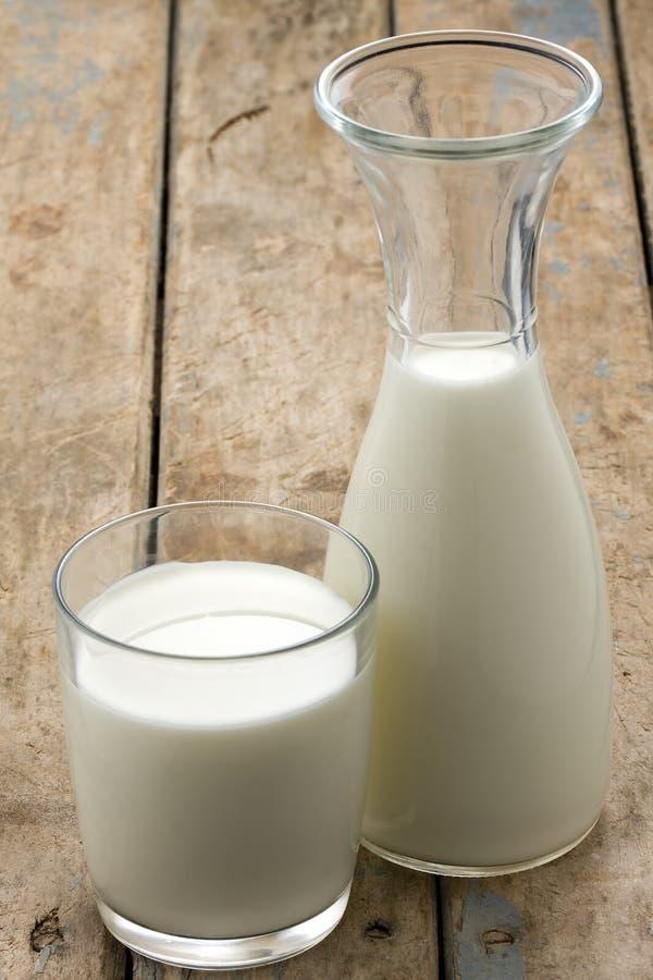 Glaskrug und Glas mit Milch stockfotos
