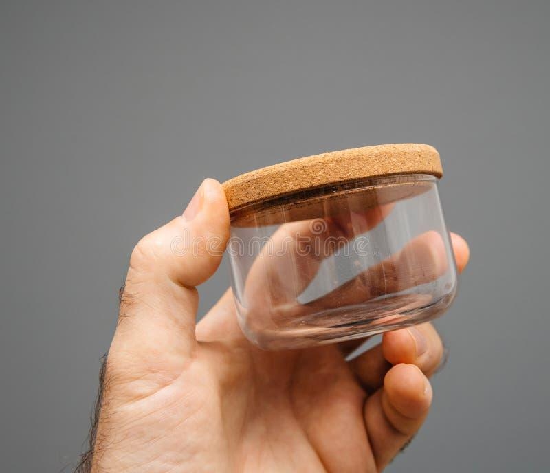 Glaskruik met cork deksel op mannelijke hand grijze achtergrond royalty-vrije stock fotografie