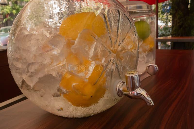 Glaskruik met een kraan, met ijs en citroenen op een hete de zomerdag die wordt gevuld royalty-vrije stock fotografie