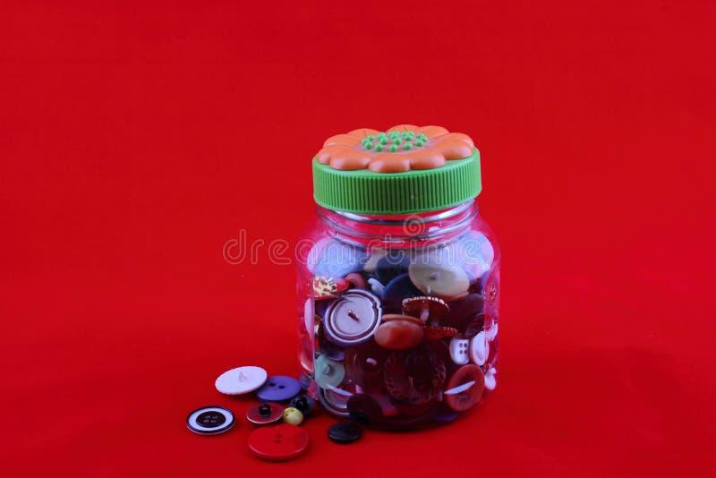 Glaskruik met een verscheidenheid van knopen die met uit gemorst wat wordt gevuld stock fotografie