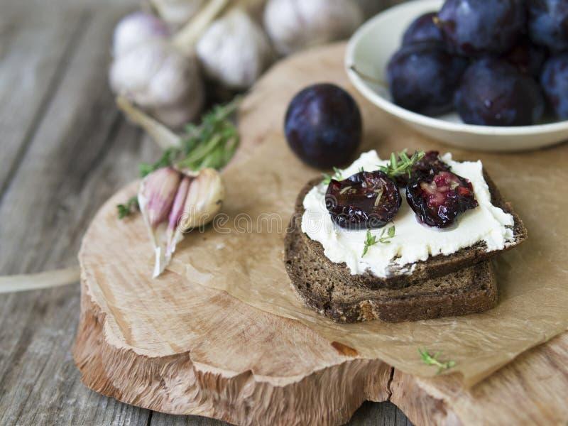 Glaskruik met gedroogde pruimen en verse rozemarijn op houten dienende raad, selectieve nadruk stock foto's