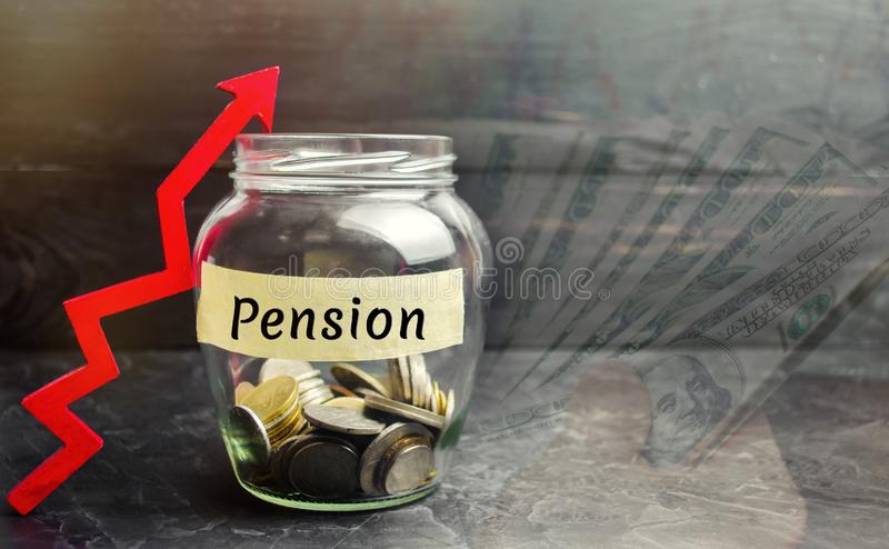 Glaskruik met muntstukken en de inschrijving 'Pensioen 'en op pijl De betalingen van het verhogingspensioen Besparingsgeld, pensi royalty-vrije stock fotografie