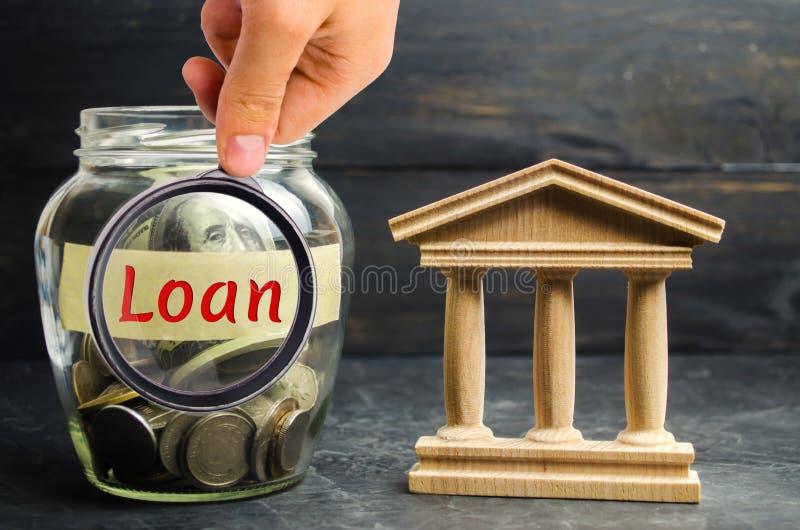 Glaskruik met muntstukken en de woordlening en een gebouw van de staat Borrow het geld, neemt een lening of een krediet van een b royalty-vrije stock afbeelding