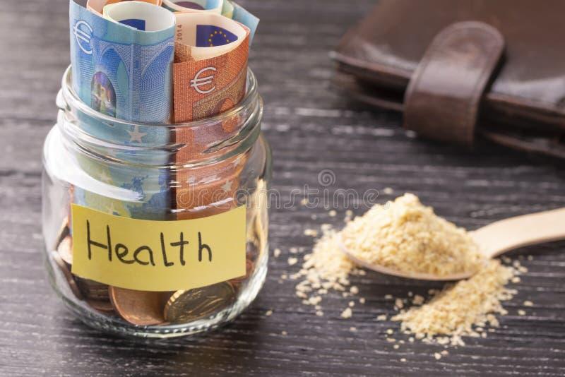 Glaskruik met muntstukken en euro bankbiljetten met de inschrijvingsgezondheid Een handvol ontkiemde tarwezaden royalty-vrije stock afbeeldingen