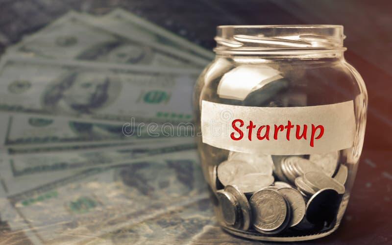 Glaskruik met muntstukken en het woord 'Opstarten ' Het concept het opheffen van fondsen voor een opstarten Liefdadige bijdragen  royalty-vrije stock fotografie