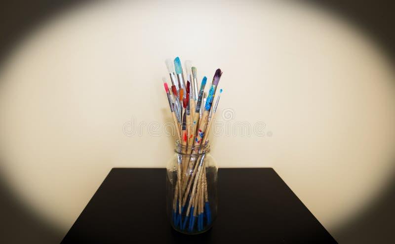Glaskruik met verf bevlekte penselen wordt gevuld dat stock afbeelding